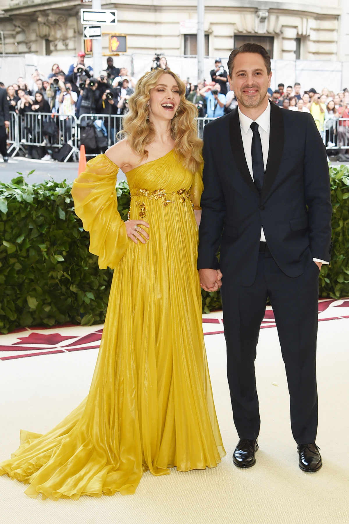 La actriz Amanda Seyfried con un vestido asimétrico y corte imperio de Prada junto a su pareja Thomas Sadoski.